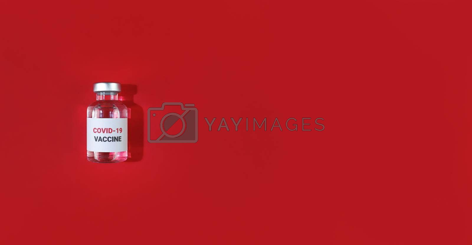 Vial with covid19 vaccine on a red background. Medical flat lay with copy space.