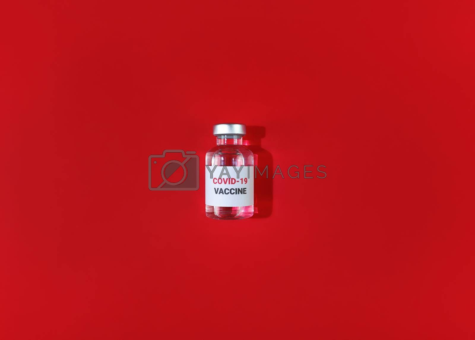 Vial with covid 19 vaccine on a red background. Medical simple flat lay.