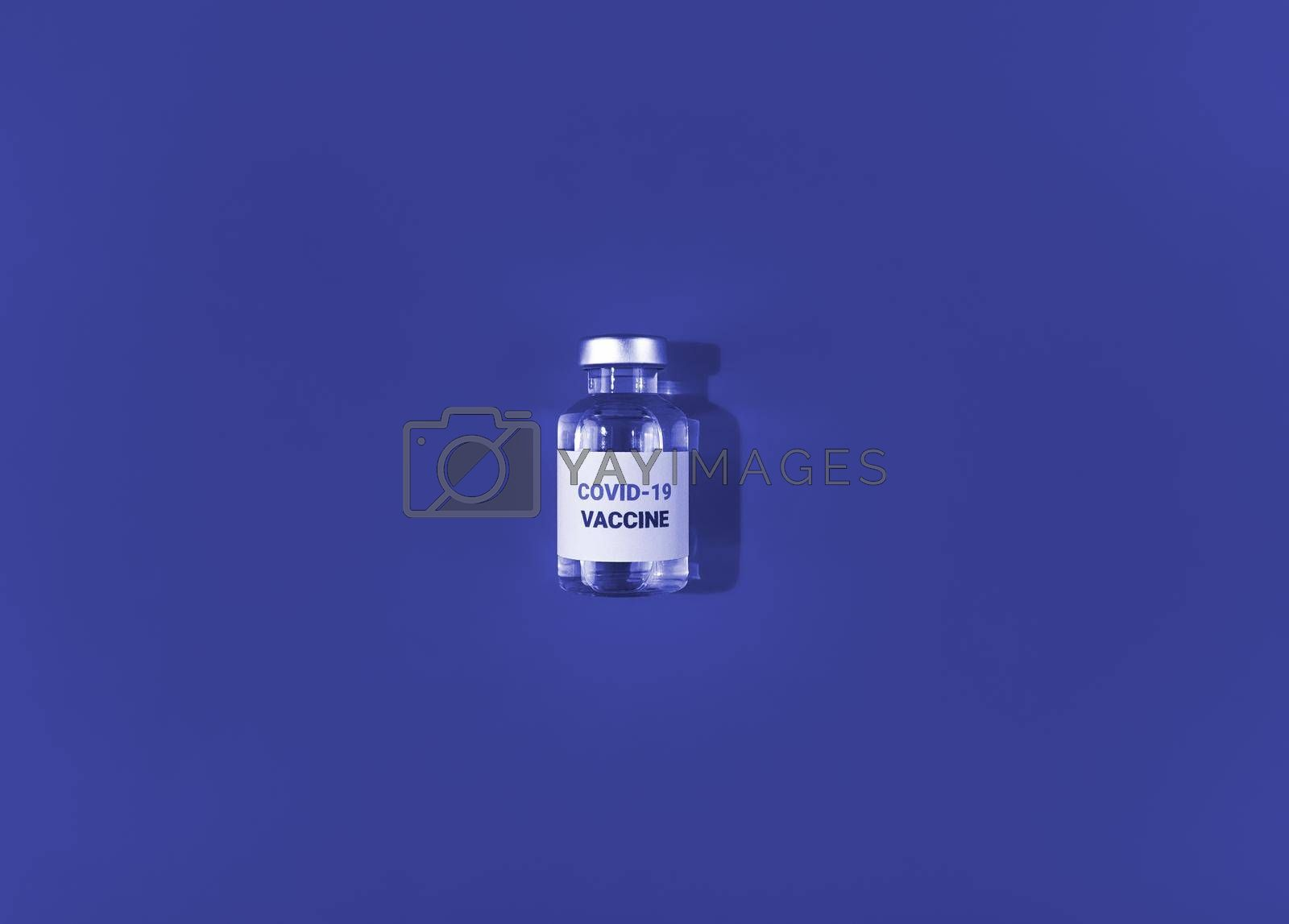Vial with covid 19 vaccine on a blue background. Medical simple flat lay.