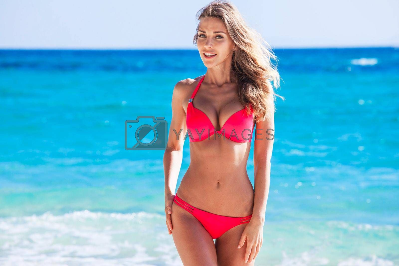 Happy tanned girl in red bikini at seaside, blue sea water in background