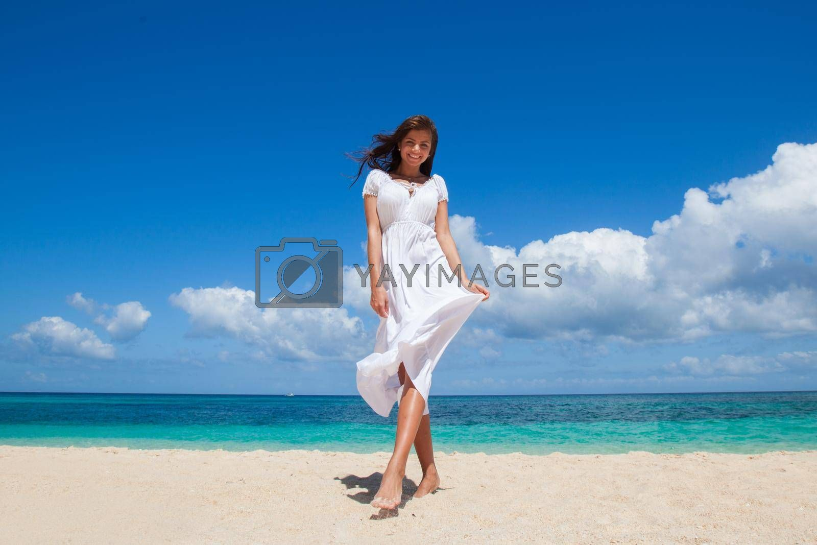 Woman in white dress walking on tropical beach, tropical sea on background