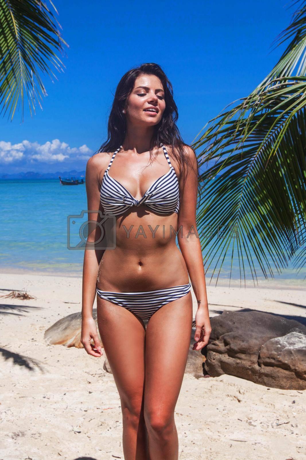 Happy woman in bikini on beach in Thailand
