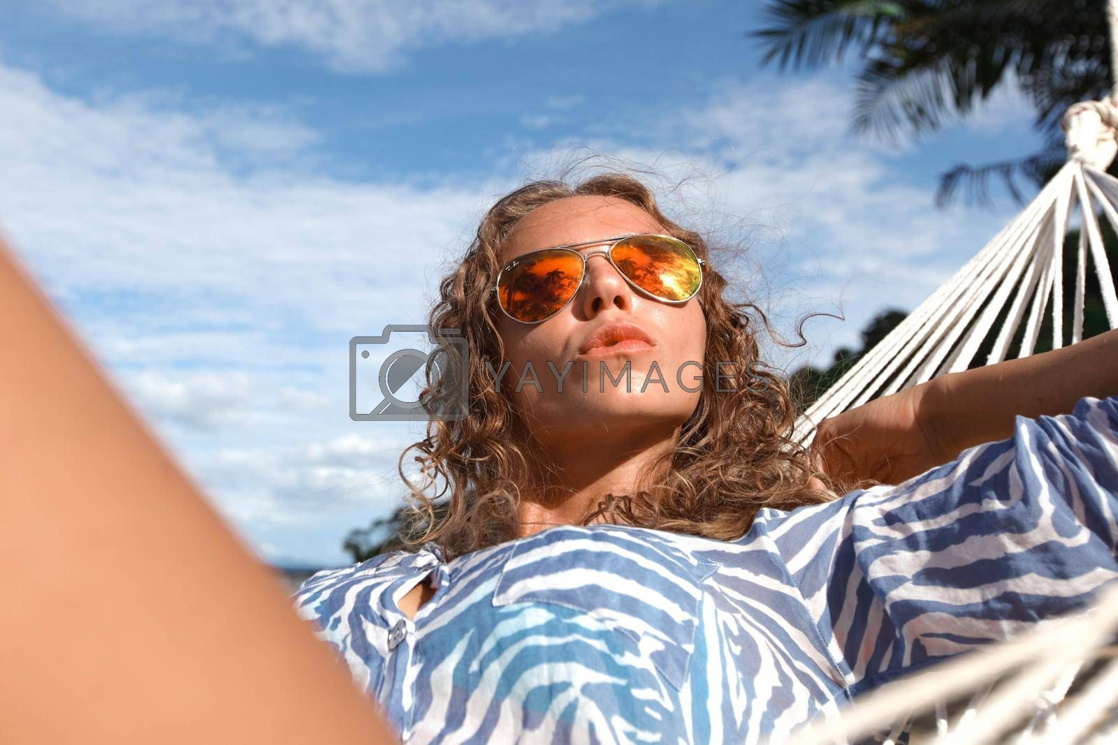 Young beautiful woman resting in hummock on tropical beach