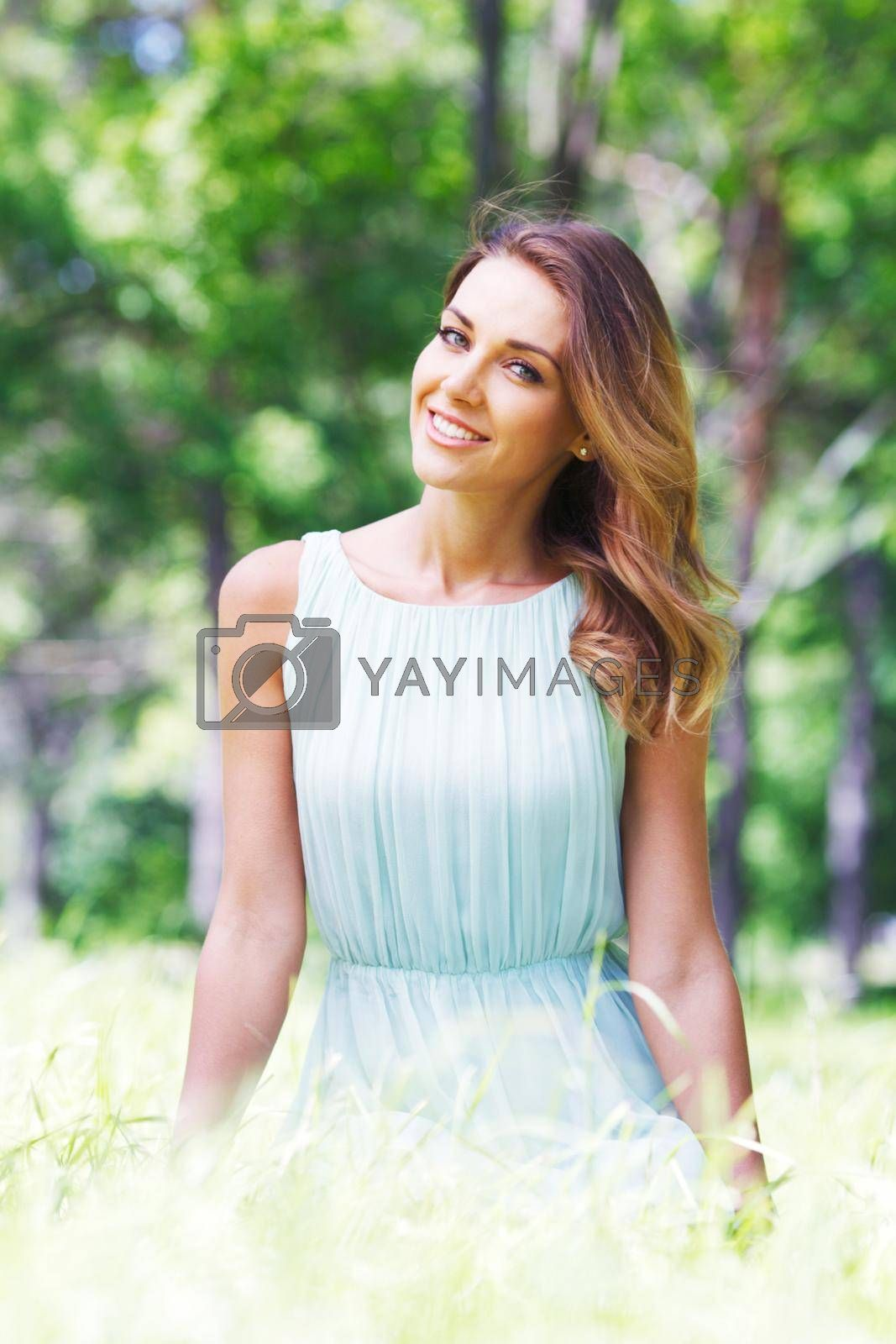 Beautiful young woman in blue dress sitting on grass