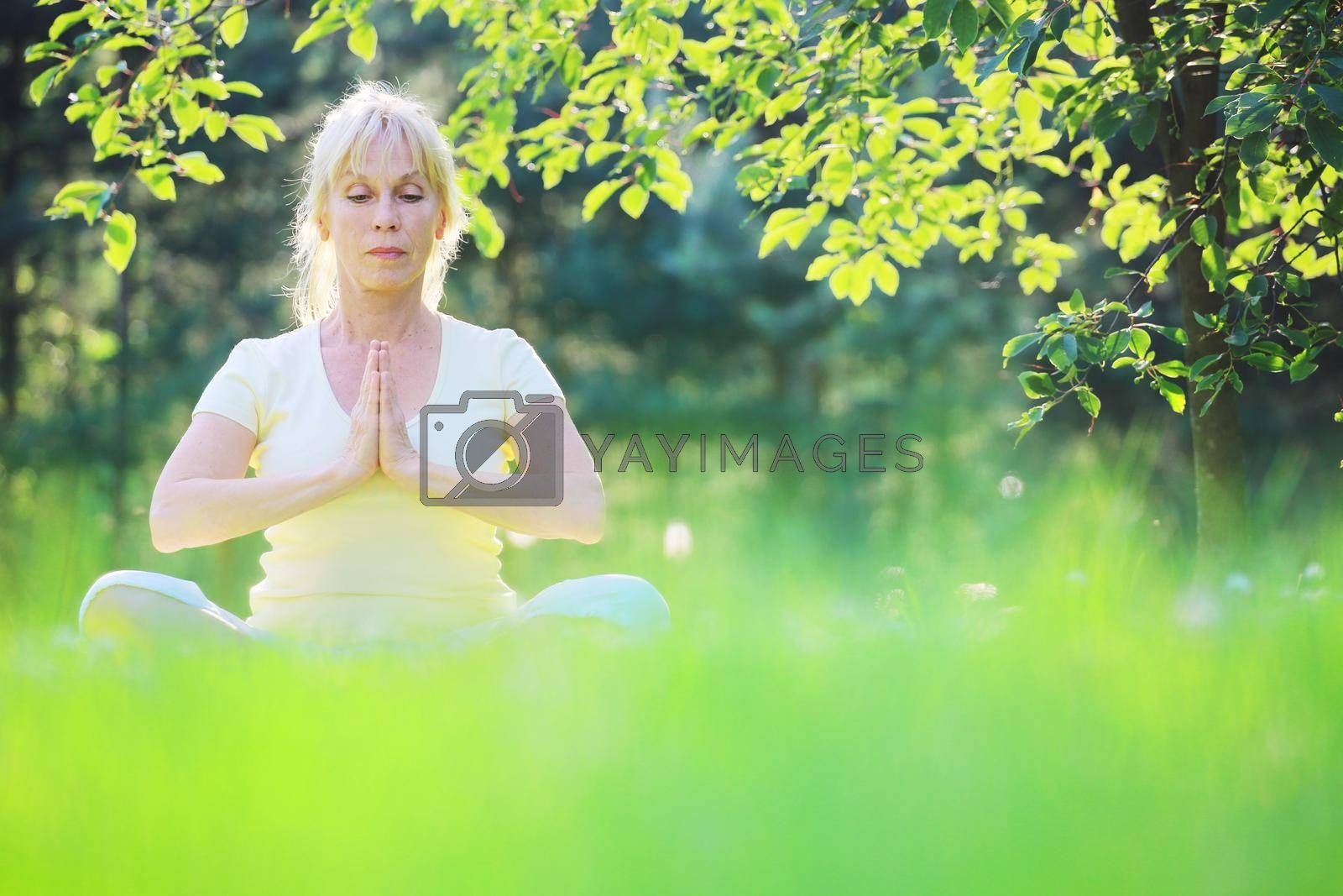 Beautiful mature woman in lotus yoga position in summer park