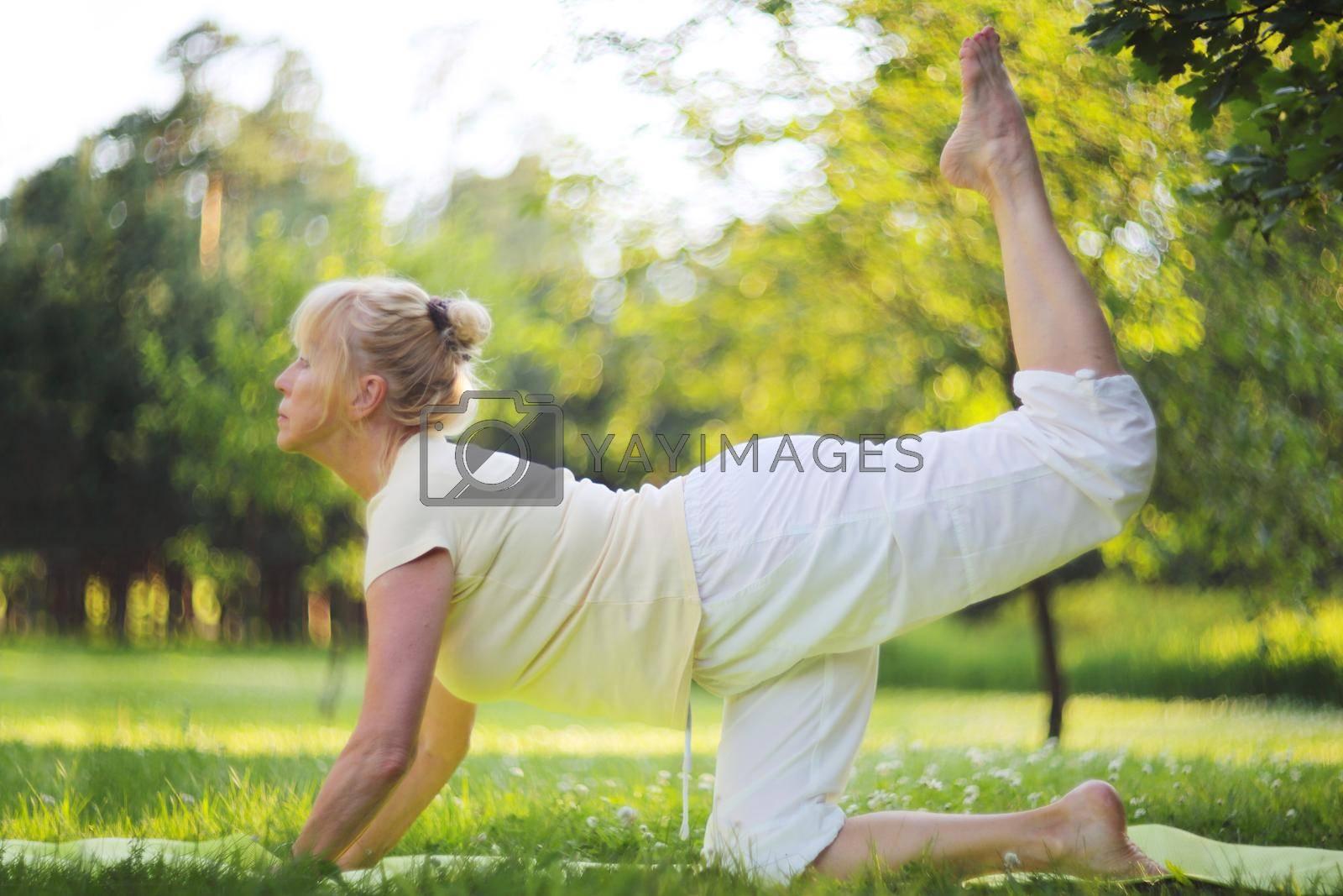 Beautiful mature woman practice yoga in summer park