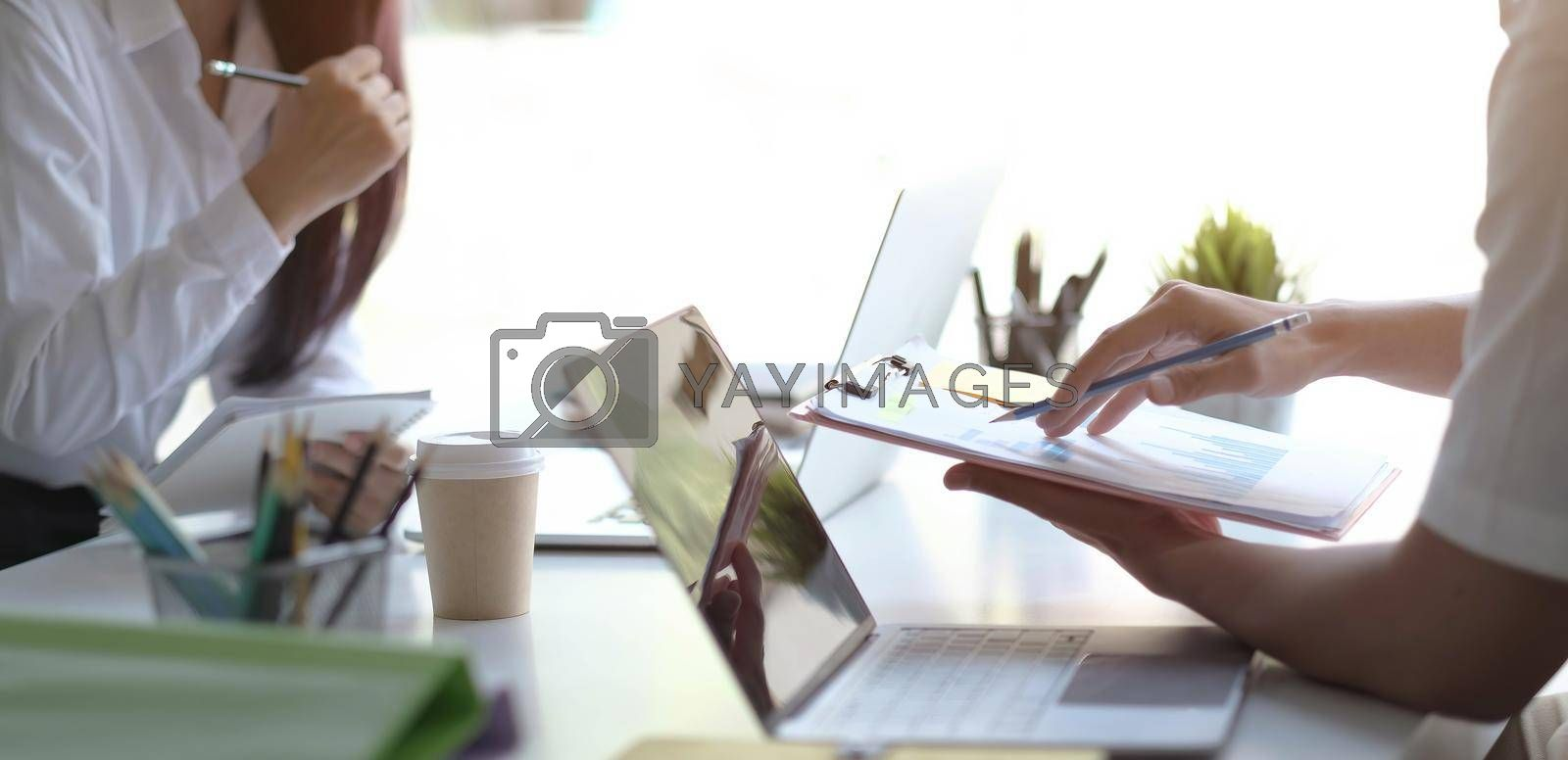 Team Businessman holding pencil working on financial report and business woman holding pens and holding paper in office..