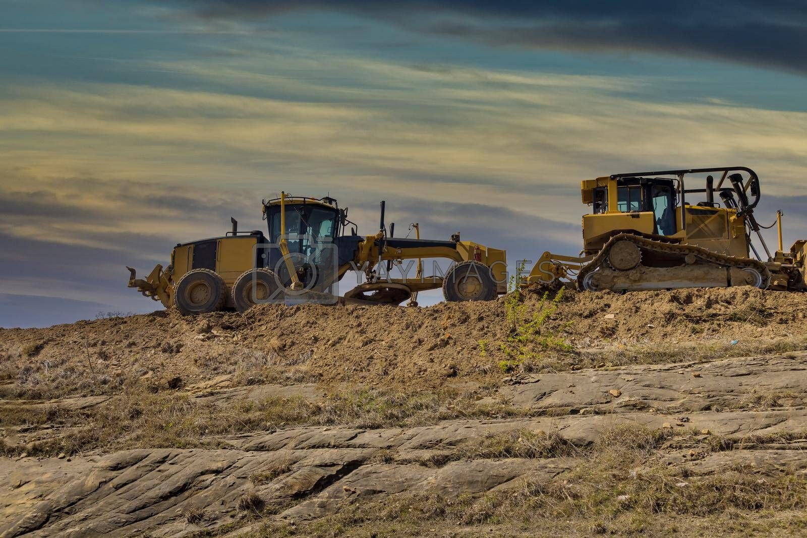 Under construction of a new asphalt road. The excavators, graders working on the new road construction site