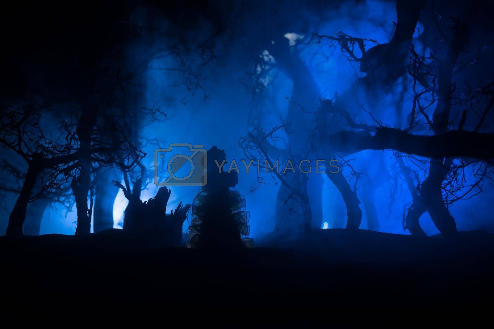 Alone girl in the dead forest at misty night. Silhouette of girl standing between trees under moonlight. Horror Halloween concept. Selective focus.