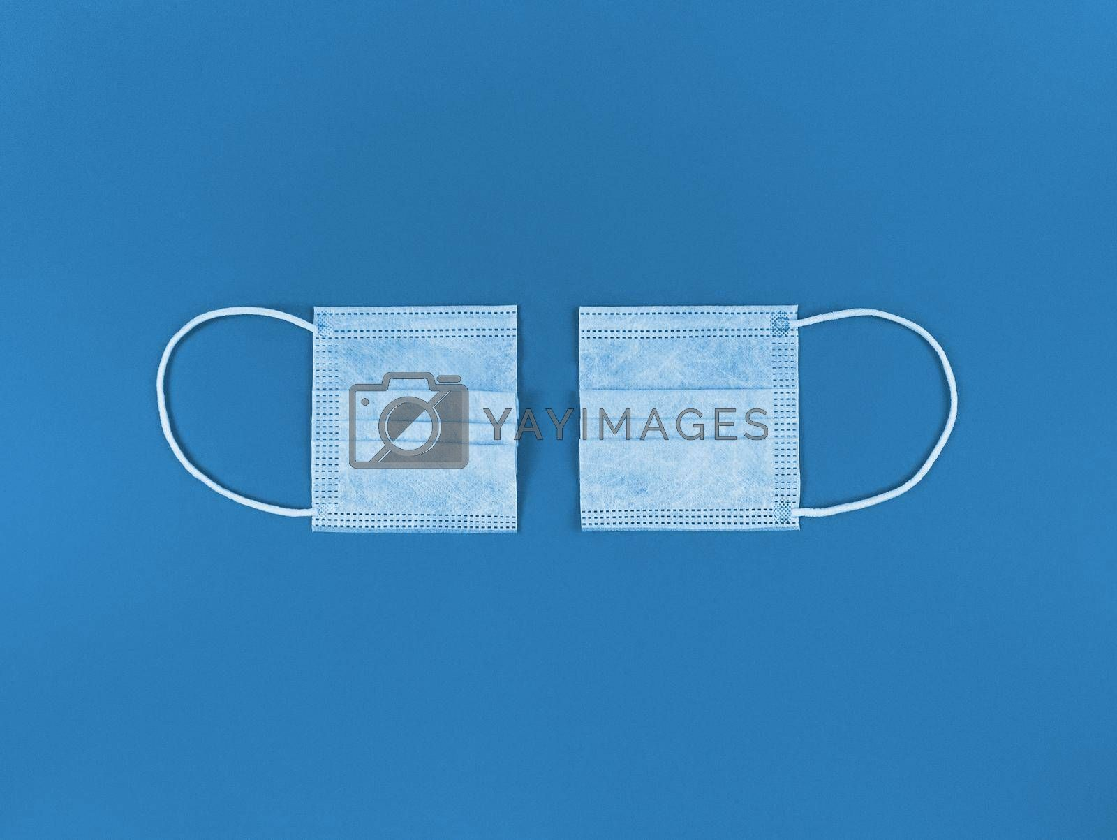 Medical disposable face mask cut in half on blue background.