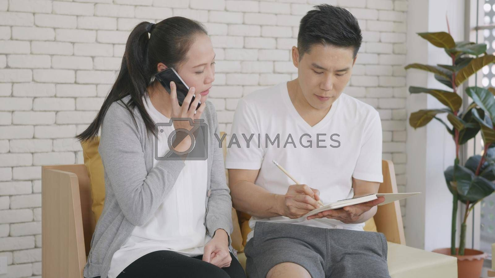 Happy Asian family couple husband and wife working confirming booking having talking call phone conversation and making writing notes of information together from home in living room.