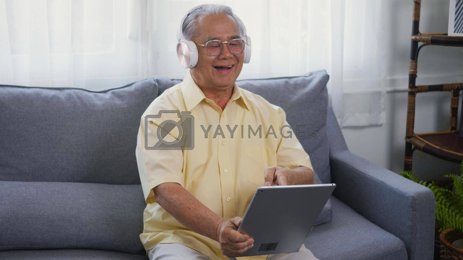Old man grandfather smile with eyeglasses relaxing wear headphones is listening to music using a digital tablet, Asian happy senior old gray-haired sitting in living room on sofa at home video call