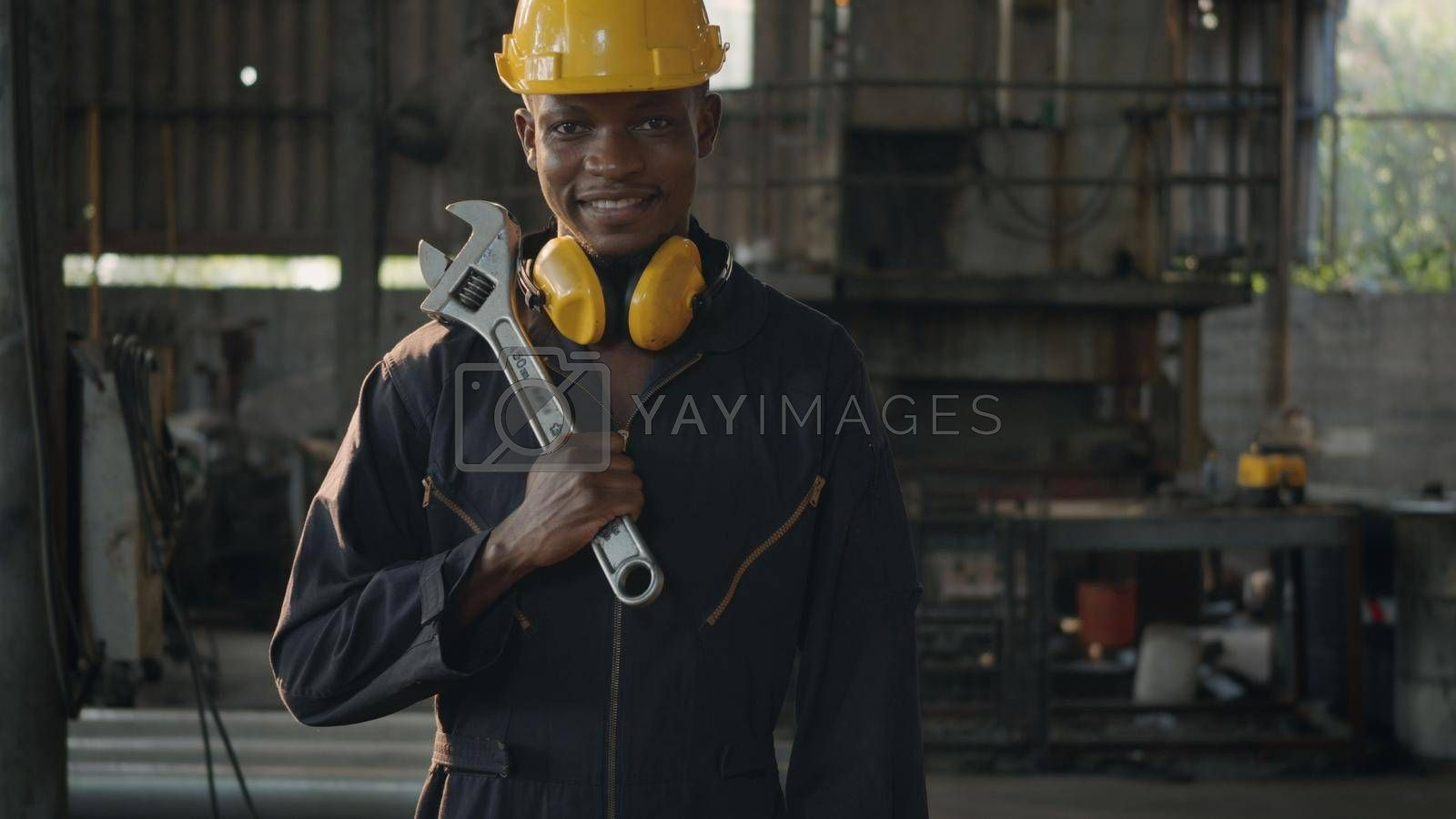Portrait American industrial black young worker man smiling with helmet and ear protection in front machine, Engineer standing holding wrench on his shoulder at work in industry factory.