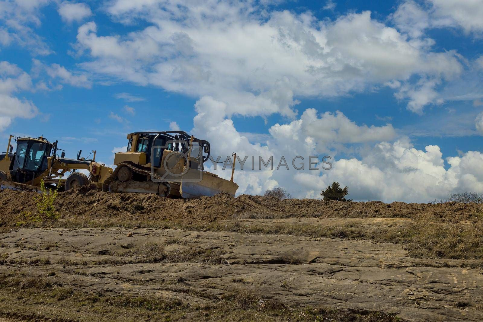 The excavators, graders in road working on the under construction site of a new road.