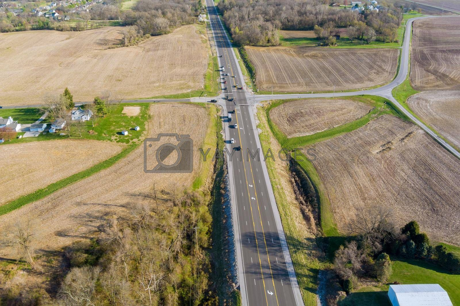 View of an aerial perspective a country asphalt road through agricultural fields, in the Caseyville Illinois on USA