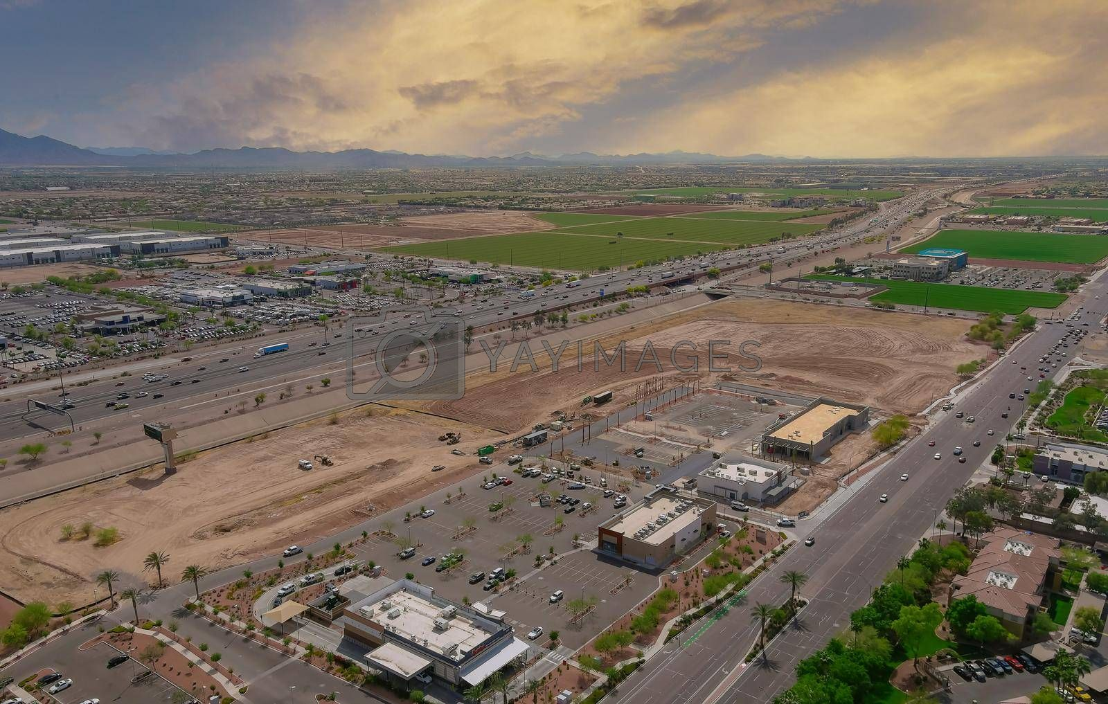 Aerial view shopping district center and parking lot in Avondale small town major road highway view overlooking desert near on state capital Phoenix Arizona USA.