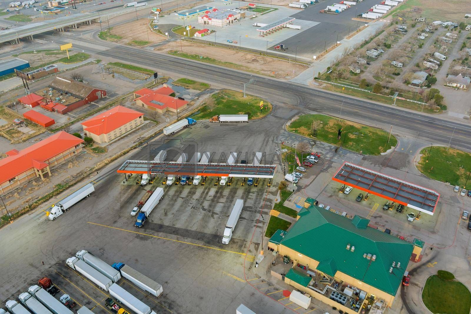 Drone view the automotive large over road semi-trucks at fueling station of the highway on USA