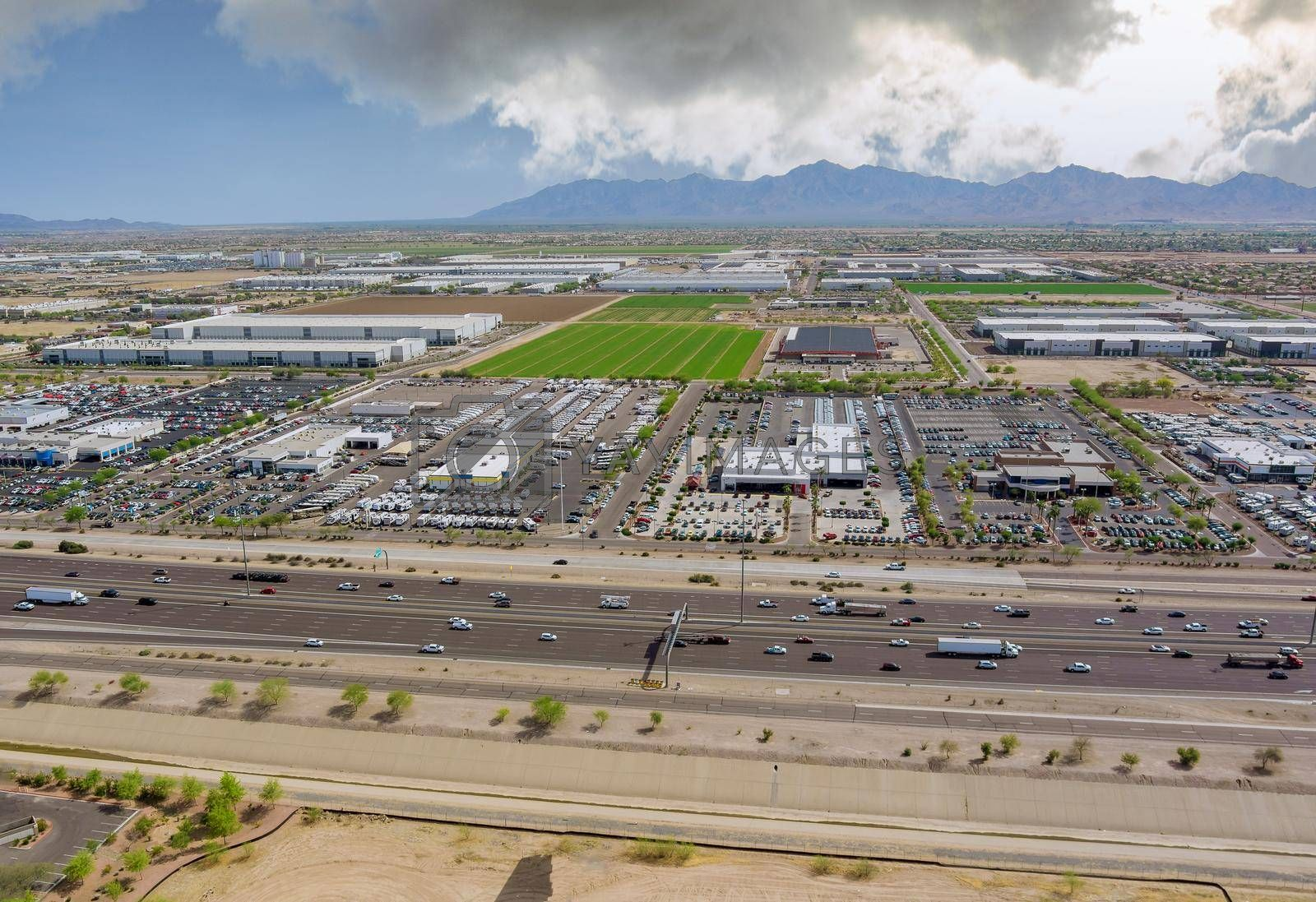 Aerial top view of typical a Avondale small town shopping center with big parking lot a major freeway near Phoenix Arizona AZ US