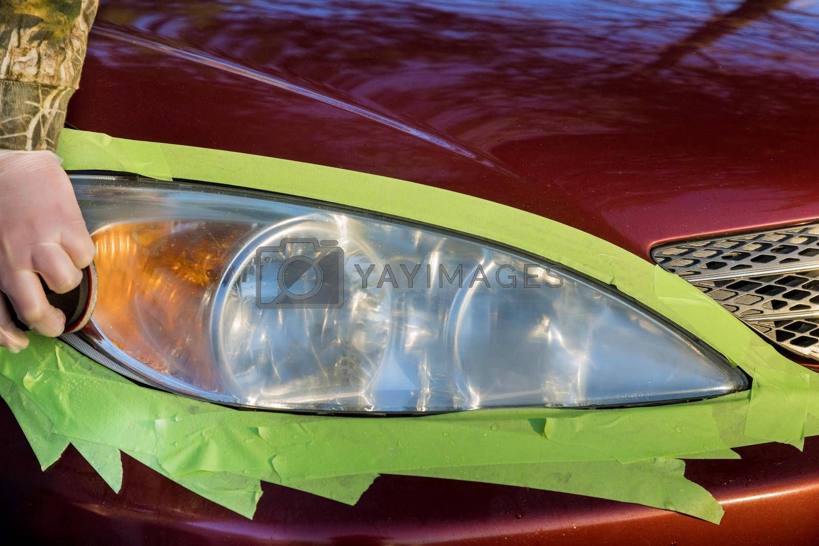 Royalty free image of Detailing of car headlights with polishing machine with service station by ungvar