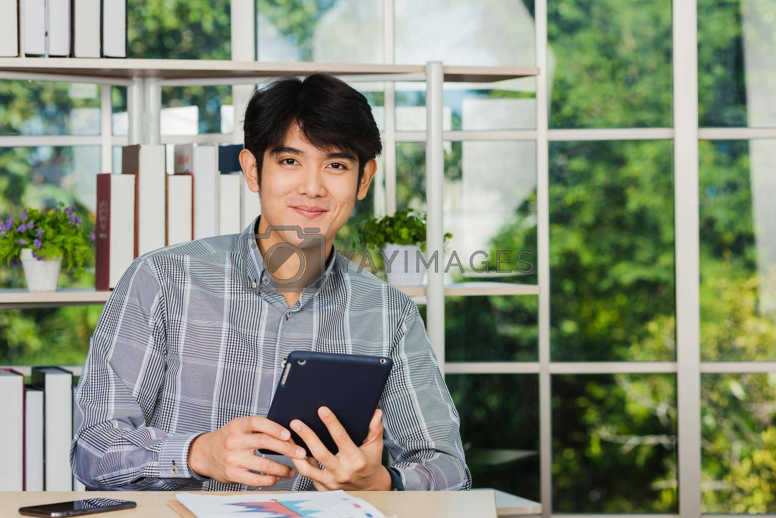 Asian young businessman sitting on desk office he smiles and working on a new tablet computer, the confident young handsome man using touchpad checking his mail
