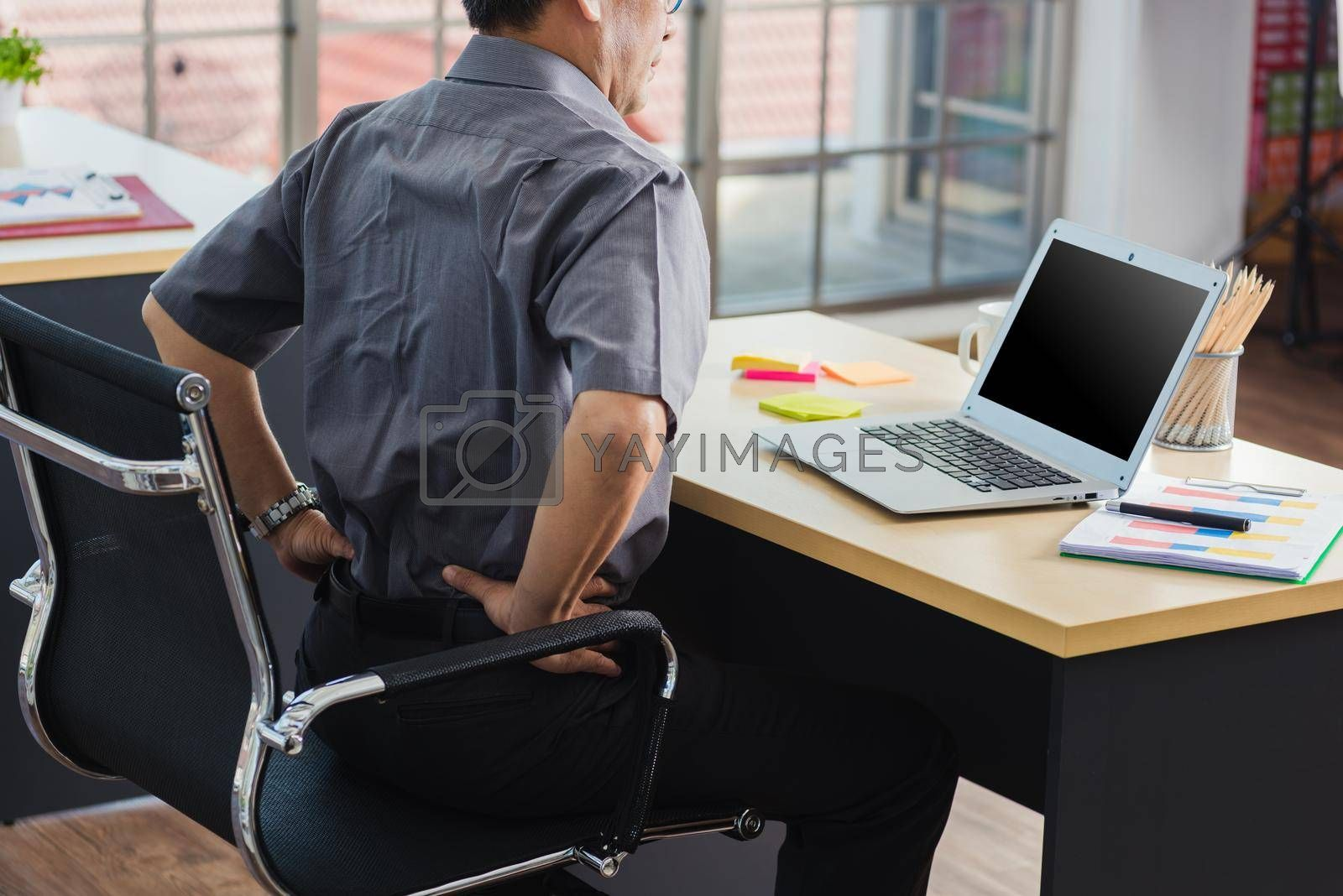 Asian hard senior businessman working with laptop computer has a problem with back pain. Old man feeling pain after sitting at desk long time, Healthcare and medicine office syndrome concept