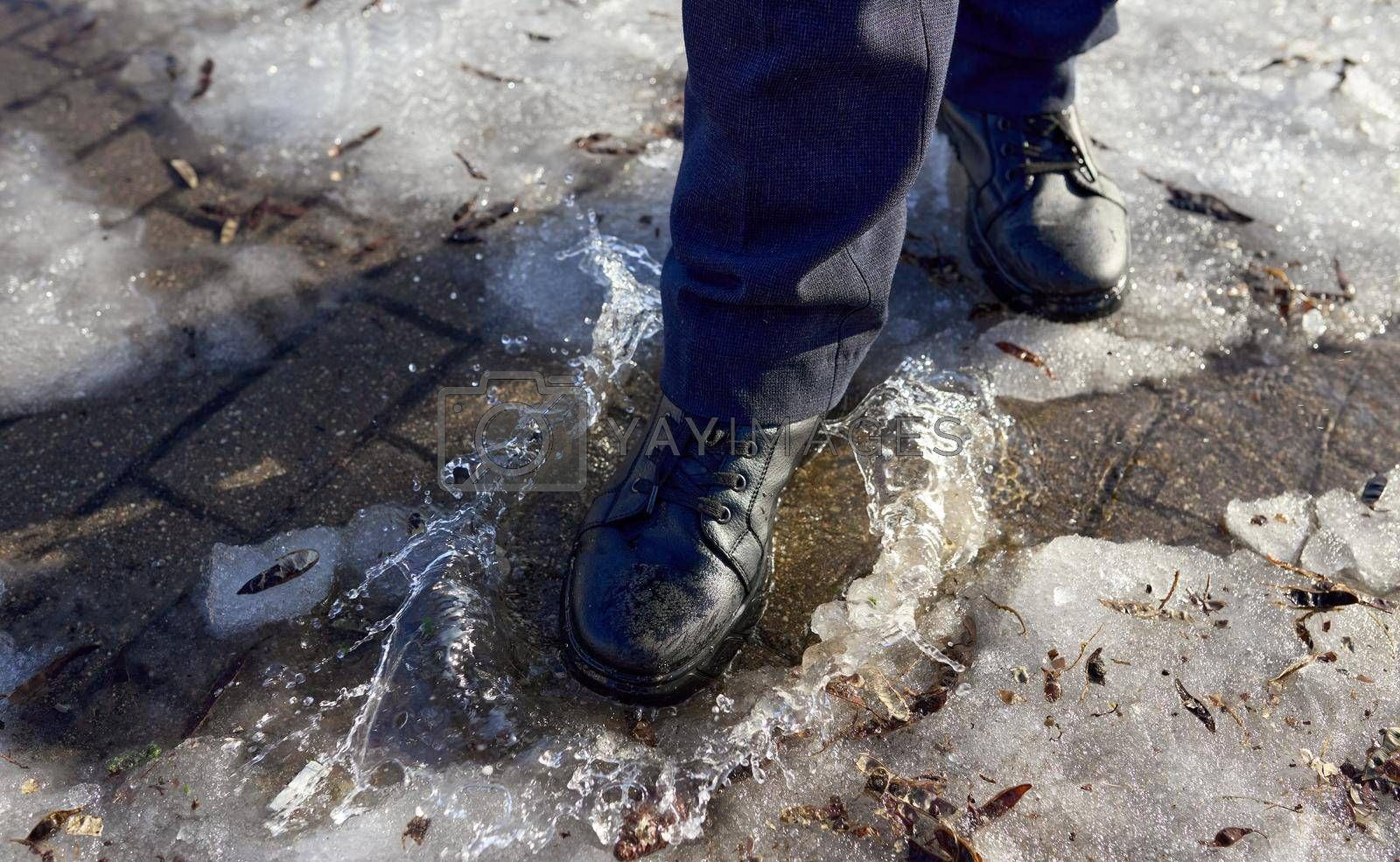Male feet in shoes walk on a puddle of melted snow. Selective focus