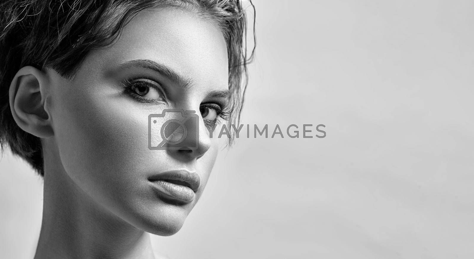 Monochrome portrait of a young attractive woman in the studio on a light background
