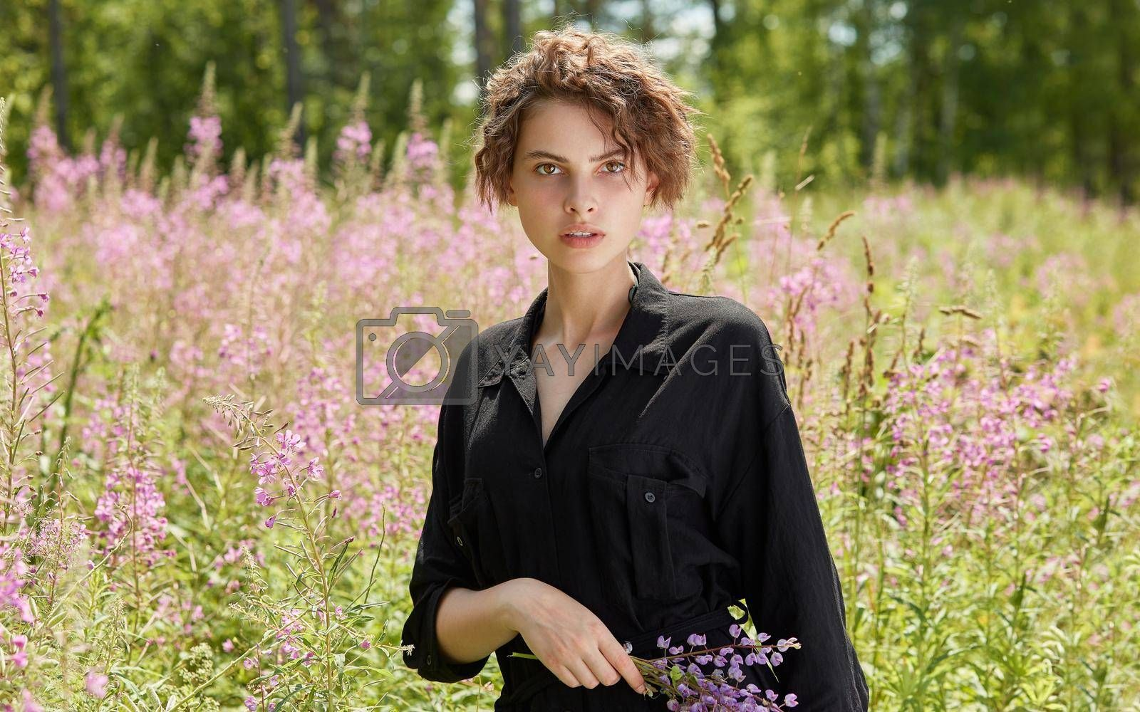 A young woman against the background of blooming Ivan-tea on a bright sunny summer day.The concept of youth