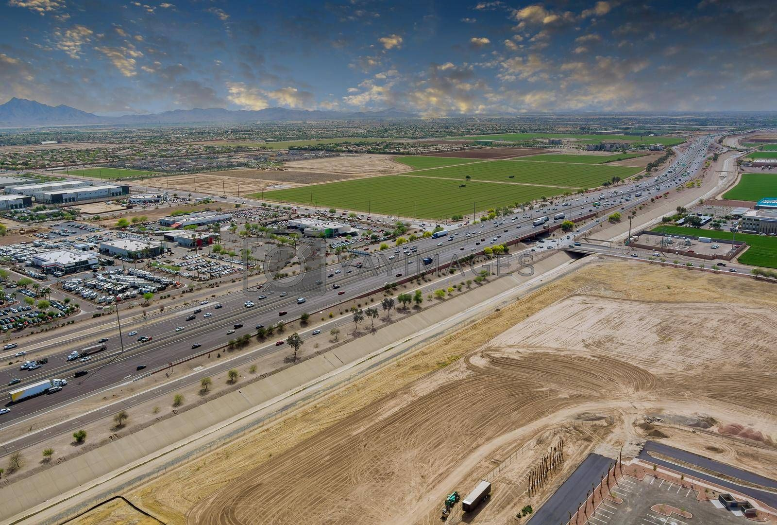 Aerial view shopping district center and parking lot in Avondale small town panorama view freeway interchange the during rush hour near Phoenix Arizona USA.