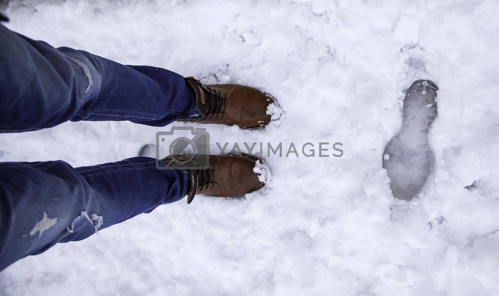 Detail of men's boots on a snowy day in winter, cold and ice