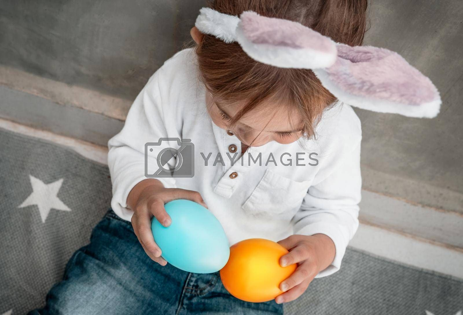 Cute Little Baby Dressed as Festive Bunny Playing with Colorful Decorative Eggs. Enjoying Happy Easter Holiday. Great Christianity Holiday.