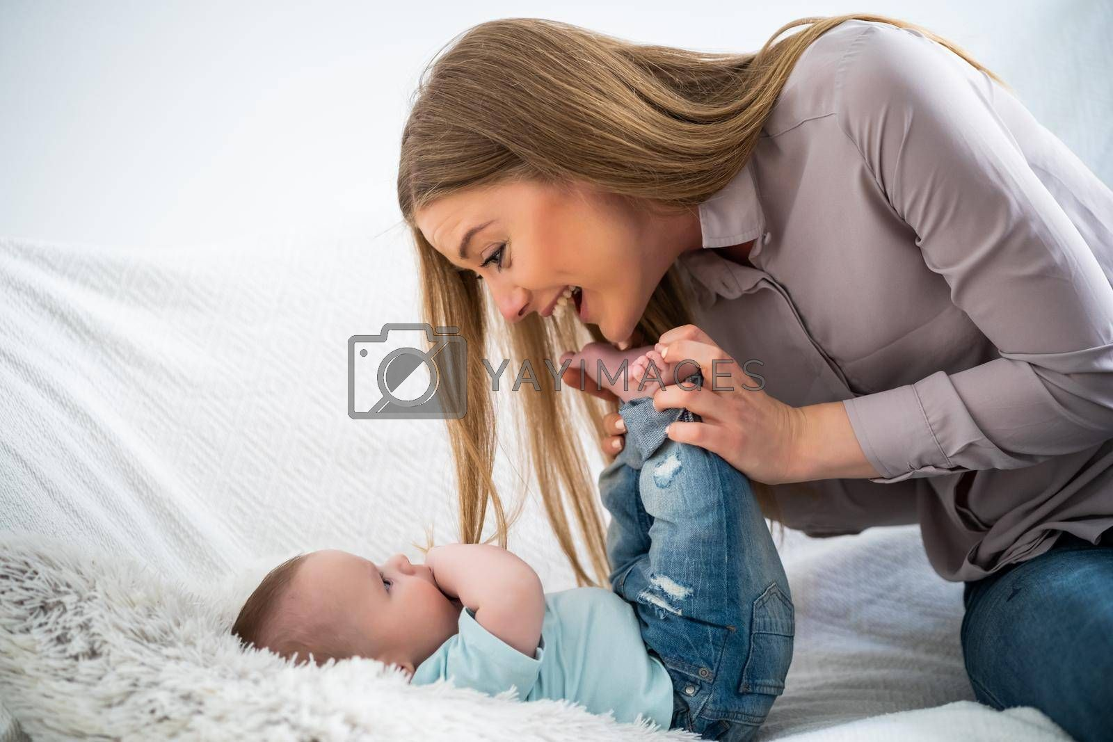 Happy mother and her baby boy playing at home.
