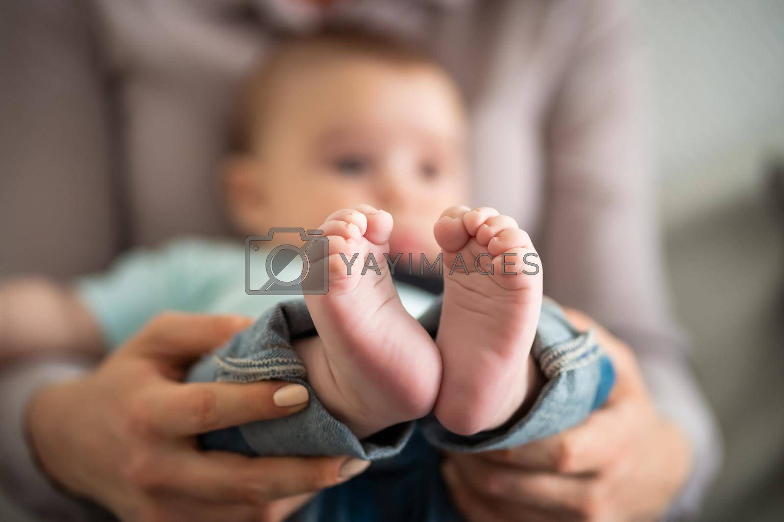 Close up image of baby feet. Mother is holding feet of her baby boy.