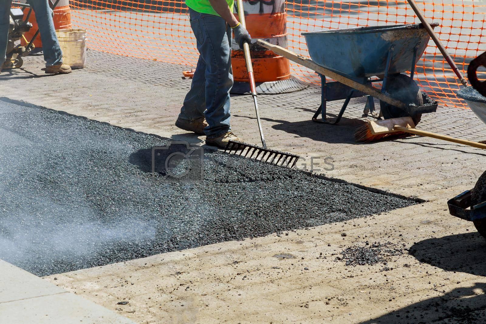 Construction site is worker laying new asphalt road on rolling fresh hot asphalt