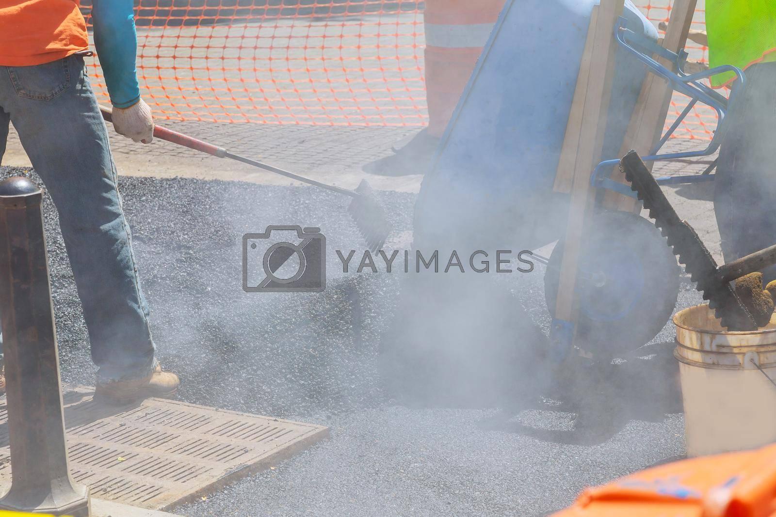 While laying asphalt road worker repair asphalt covering new road surface