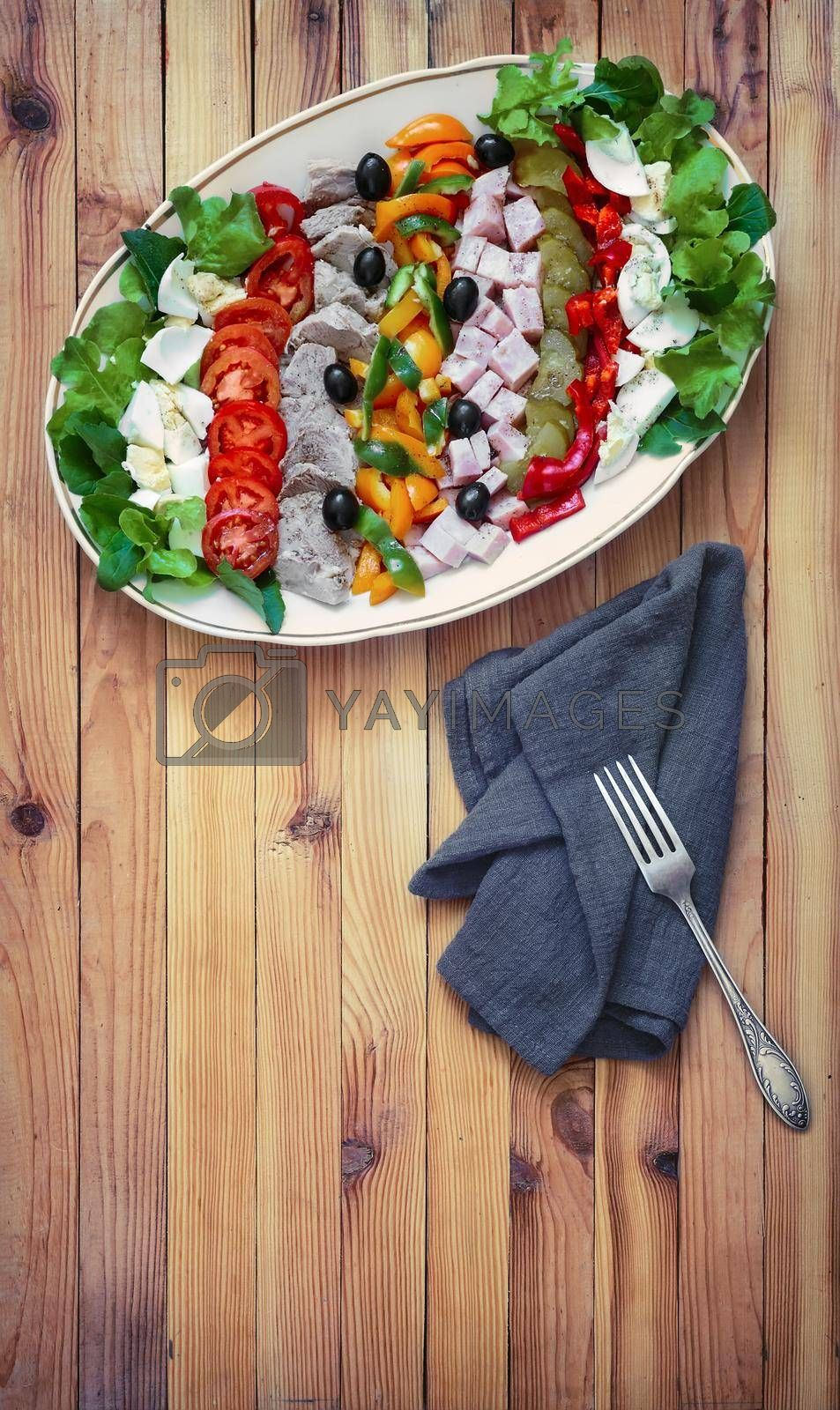 A popular dish of American cuisine - Cobb salad, consisting of greens, eggs, tomatoes, cheese, meat products, stacked in rows on a wide dish and poured sauce.