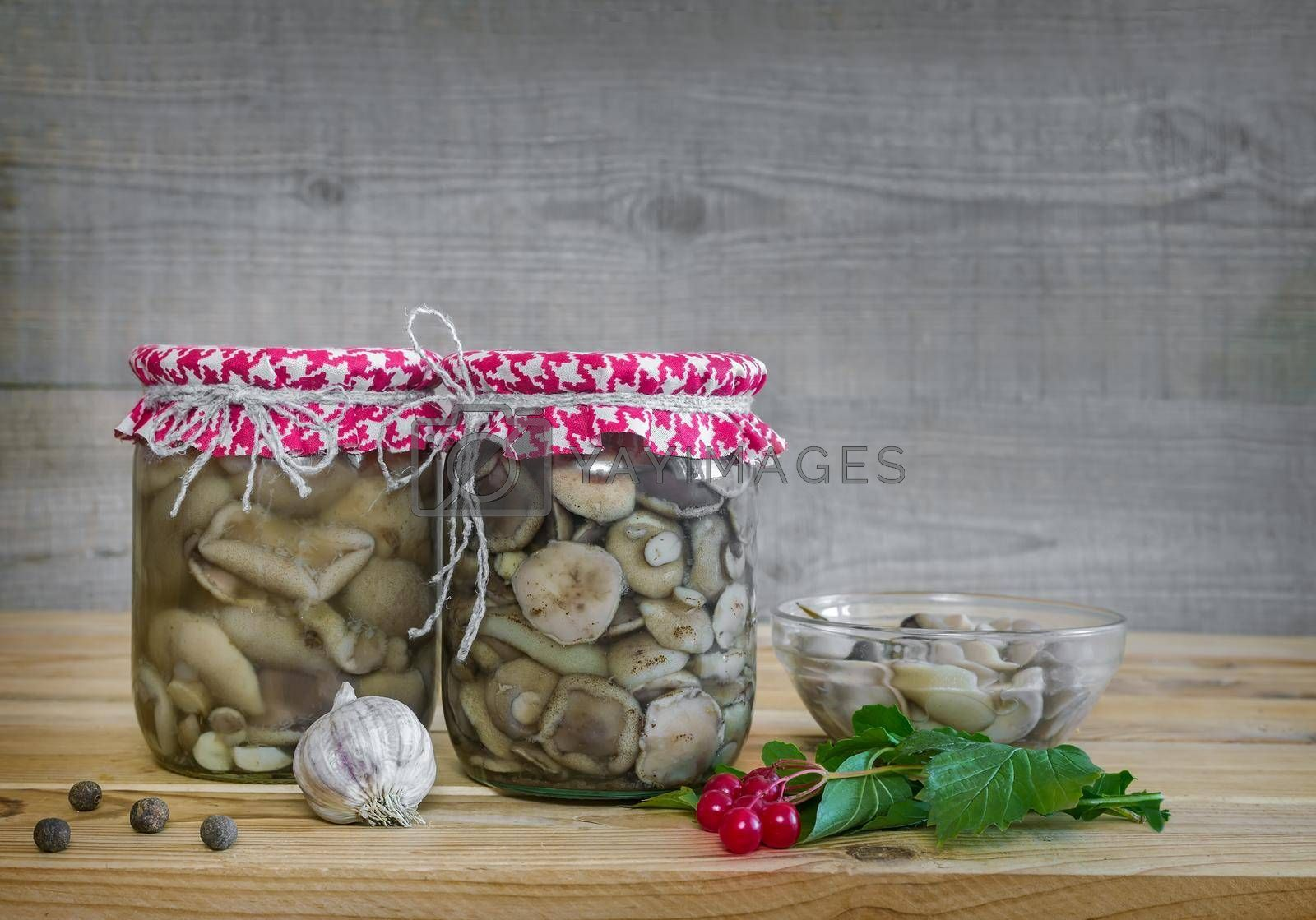 On the table with a wooden table top small glass jars with picked mushrooms. Home canning.