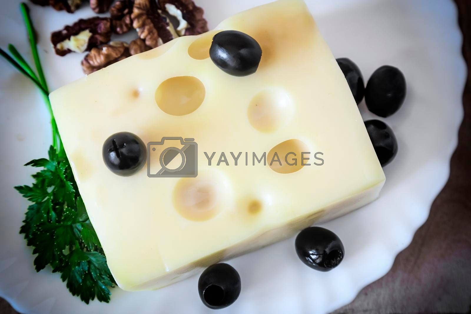 On the table on a white plate to get the cheese, walnuts and olives.