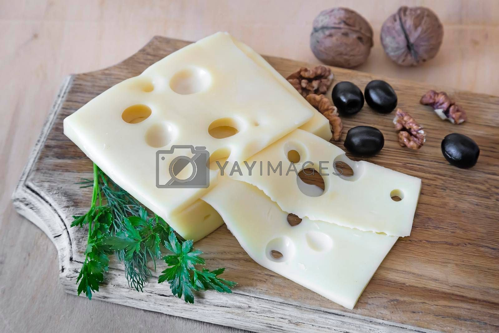 On the table on a cutting Board lies with sliced cheese, walnuts and olives.