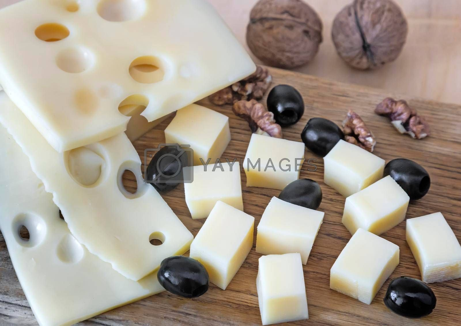 On the table-sliced cheese, walnuts and olives.