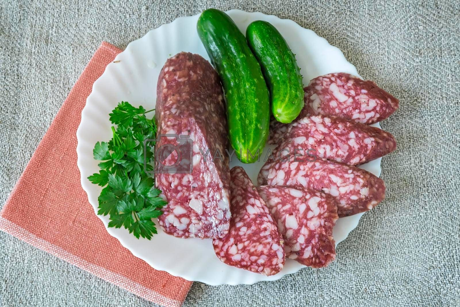 Royalty free image of Slices of sausage and cucumber on the plate. by georgina198