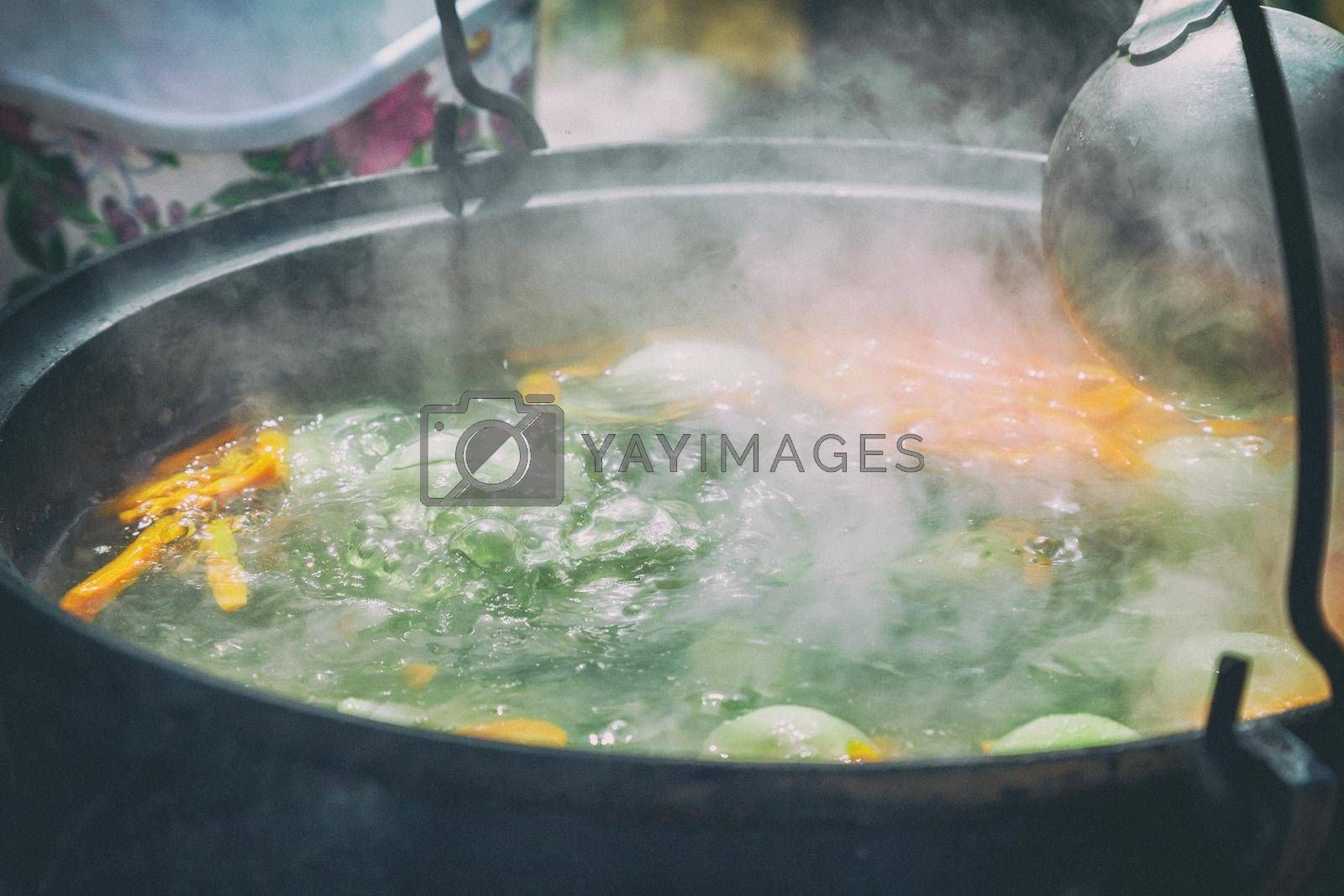 Delicious fish soup is cooked in a pot on fire. Presented close-up.