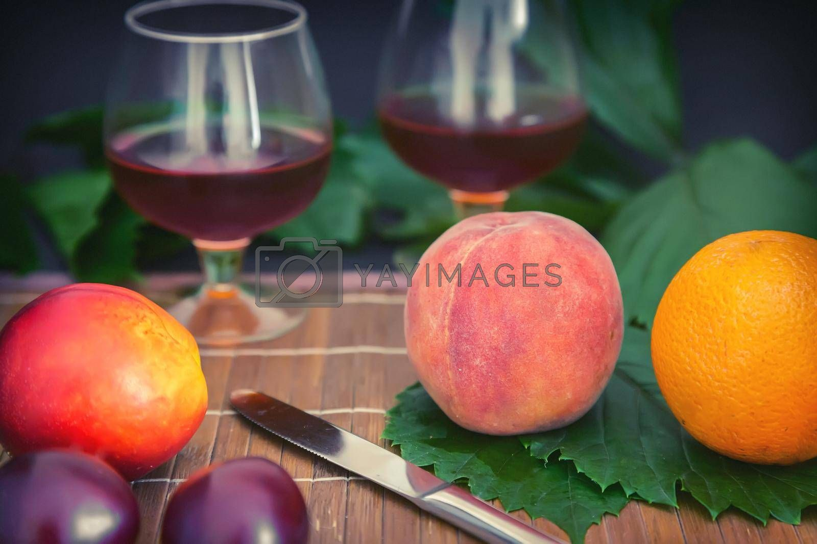 Still life: on the table on the green leaves are fruits, next to two glasses of wine.