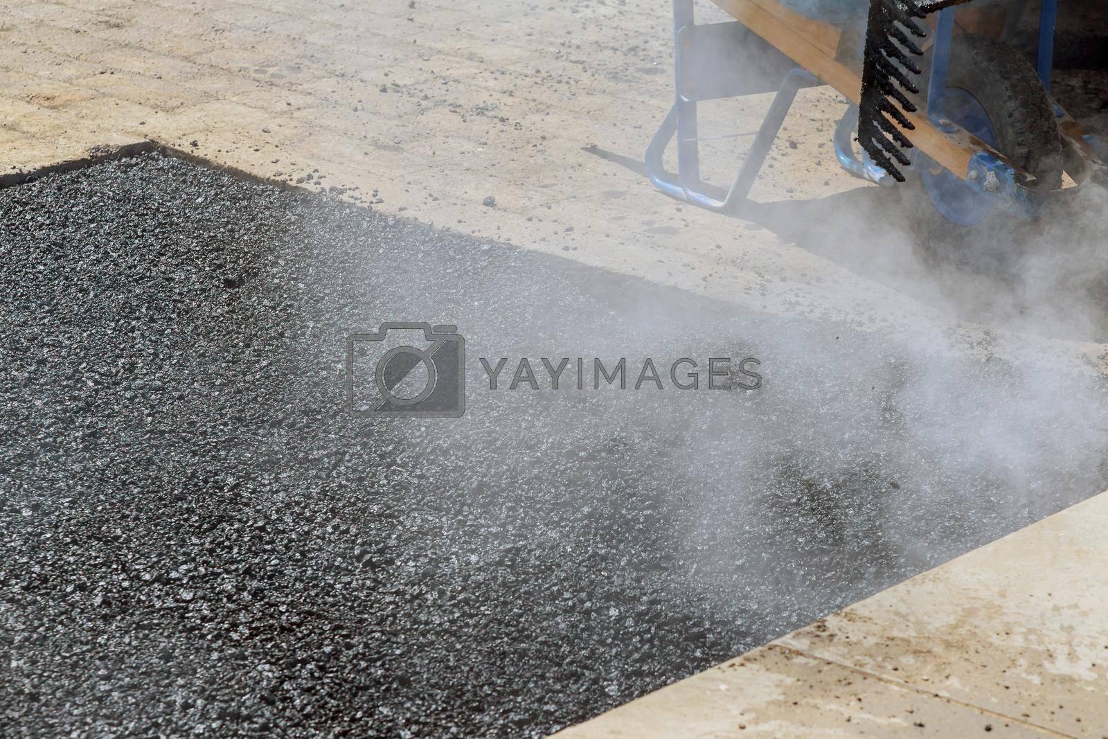 While laying asphalt new road surface road worker repair asphalt covering