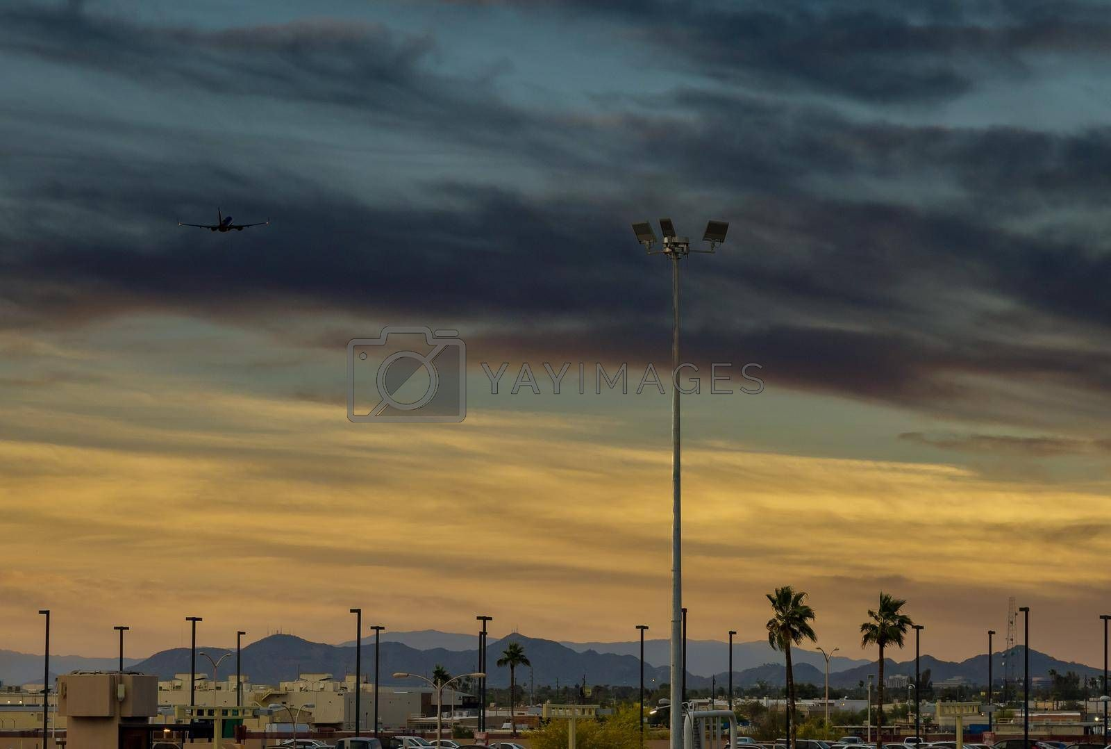 Modern international airport during sunset a passenger plane in flight away in to sky
