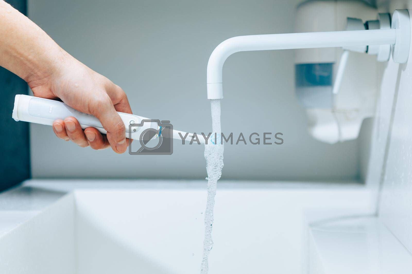 hand holding a toothbrush under flowing water from faucet in a bathroom