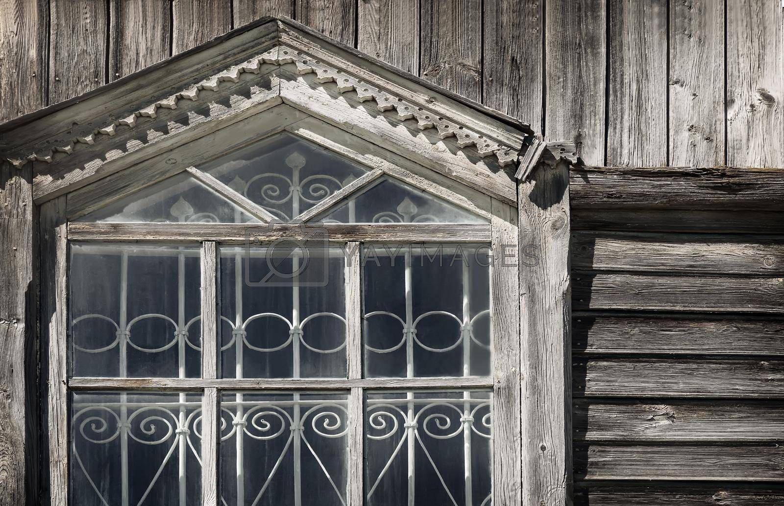 A fragment of the window of the ancient Orthodox wooden Church with wrought iron bars and carved wooden platbands