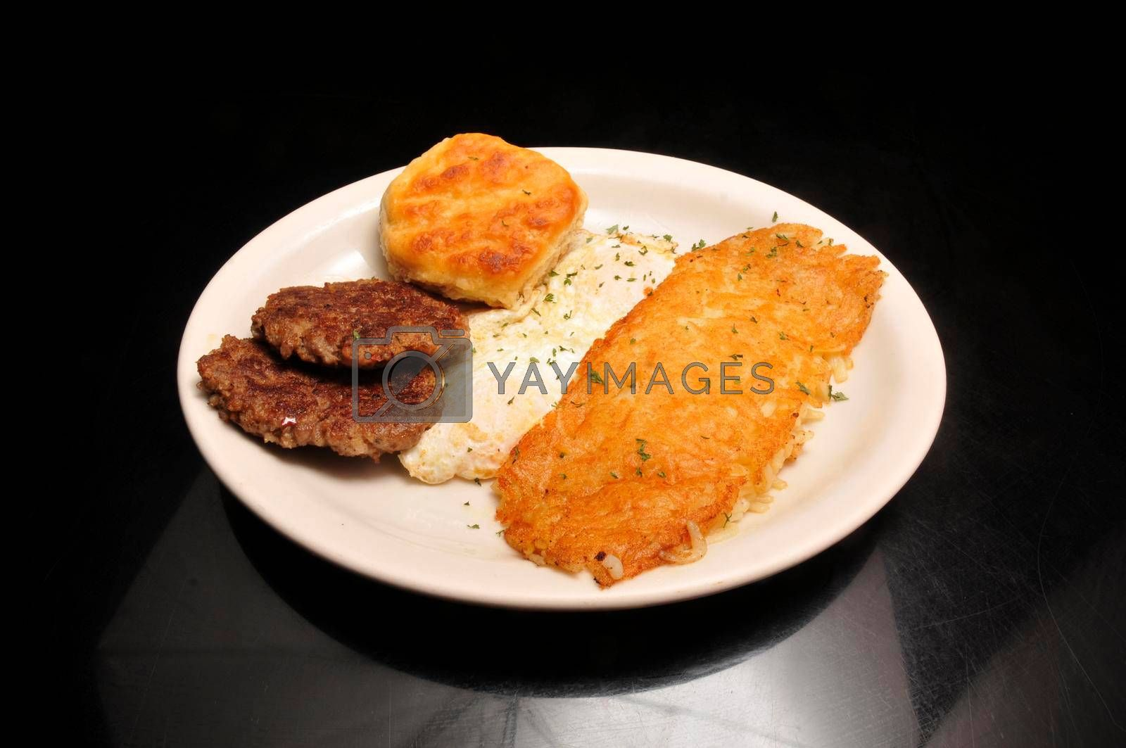 Delicious breakfast of Eggs Sausage Hash Browns and a biscuit
