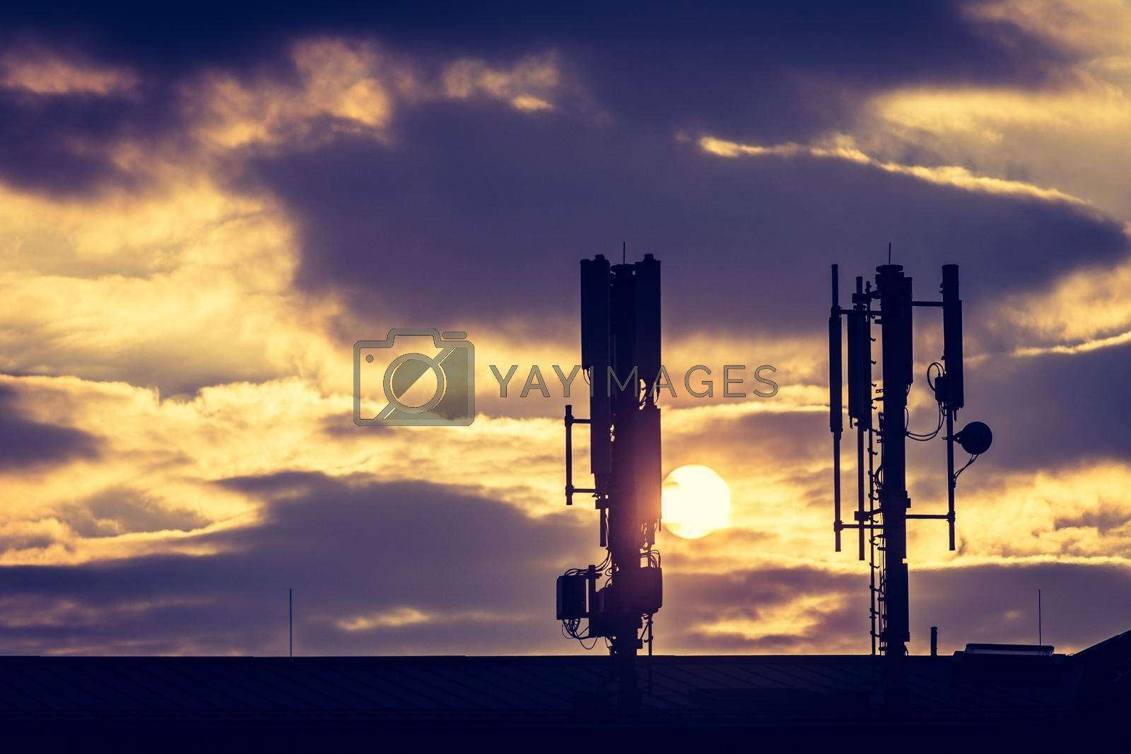 Silhouette of communication or cell tower on the rooftop of a building, evening sunshine