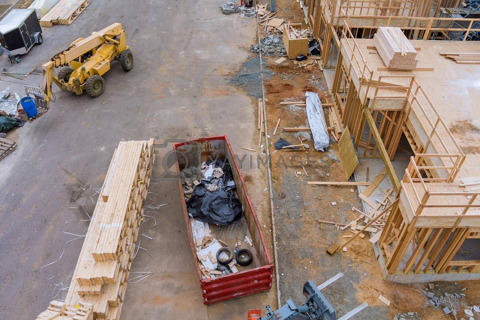 New apartments under construction home residential building development a wooden building materials stack of boards wood frame beam construction on metal container house renovation